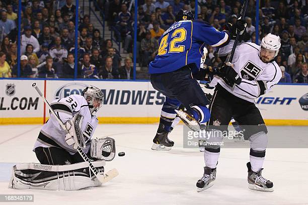 David Backes of the St Louis Blues jumps out of the way of a shot on goal against Drew Doughty of the Los Angeles Kings as Jonathan Quick of the Los...