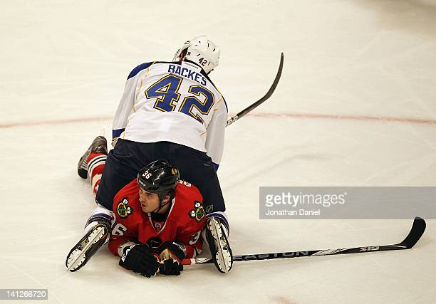 David Backes of the St Louis Blues lands on top of Dave Bolland of the Chicago Blackhawks at the United Center on March 13 2012 in Chicago Illinois