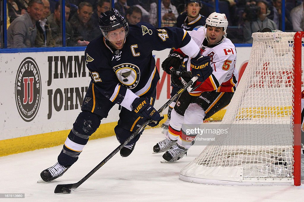 <a gi-track='captionPersonalityLinkClicked' href=/galleries/search?phrase=David+Backes&family=editorial&specificpeople=2538492 ng-click='$event.stopPropagation()'>David Backes</a> #42 of the St. Louis Blues looks to pass the puck against <a gi-track='captionPersonalityLinkClicked' href=/galleries/search?phrase=Mark+Giordano&family=editorial&specificpeople=696867 ng-click='$event.stopPropagation()'>Mark Giordano</a> #5 of the Calgary Flames during the third period at the Scottrade Center on April 25, 2013 in St. Louis, Missouri. The Blues beat the Flames 4-1.