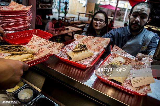 David Barquet owner and chef of the Camello Gitano Lebanese food truck right grabs orders for customers at the Street Food Center in a park in the...