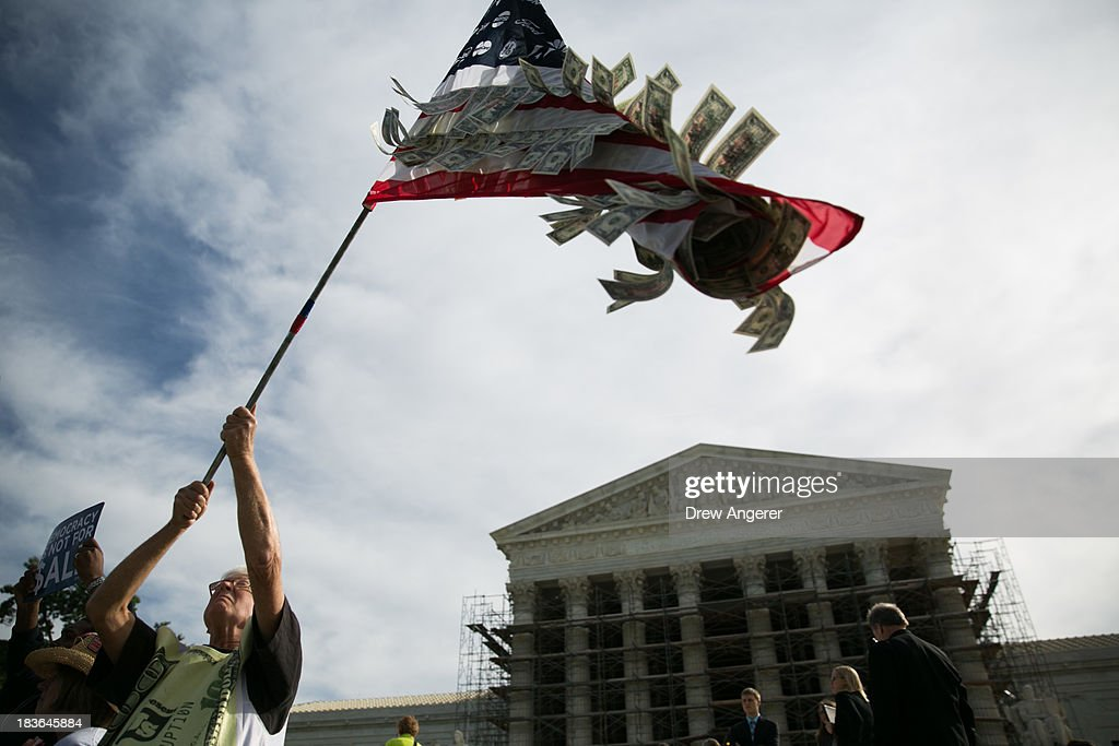 David Barrows, of Washington, D.C., waves a flag with corporate logos and fake money during a rally against money in politics, at the Supreme Court in Washington, on October 8, 2013 in Washington, DC. On Tuesday, the Supreme Court will hear oral arguments in McCutcheon v. Federal Election Committee, a first amendment case that will determine how much money an individual can contribute directly to political campaigns.