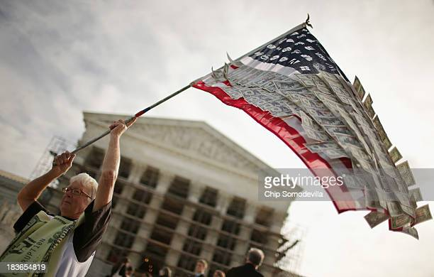 David Barrows of Washington DC waves a flag with corporate logos and fake money during a rally against money in politics outside the Supreme Court...