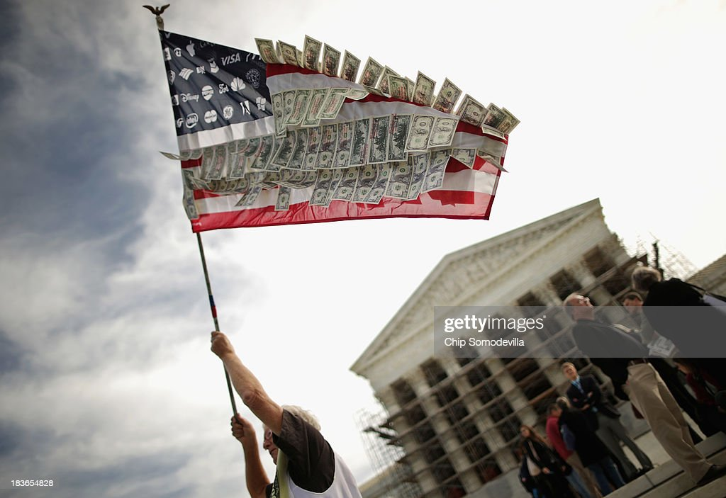 David Barrows, of Washington, DC, waves a flag with corporate logos and fake money during a rally against money in politics outside the Supreme Court October 8, 2013 in Washington, DC. On Tuesday, the Supreme Court heard oral arguments in McCutcheon v. Federal Election Committee, a first amendment case that will determine how much money an individual can contribute directly to political campaigns.