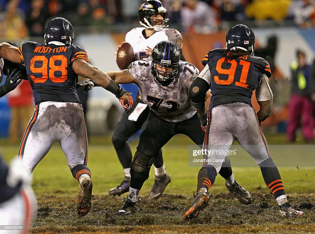 David Bass #91 and Corey Wootton#98 of the Chicago Bears rush against Marshal Yanda #73 of the Baltimore Ravens at Soldier Field on November 17, 2013 in Chicago, Illinois. The Bears defeated the Ravens 23-20 in overtime.