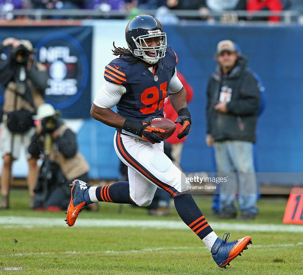 David Bass #91 of the Chicago Bears smiles as he returns an interception for a touchdown against the Baltimore Ravens at Soldier Field on November 17, 2013 in Chicago, Illinois.