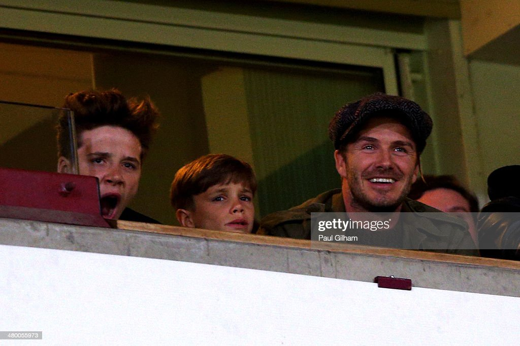 David Beckham and his sons Romeo Beckham and Brooklyn Beckham watch the action during the Barclays Premier League match between West Ham United and Manchester United at Boleyn Ground on March 22, 2014 in London, England.