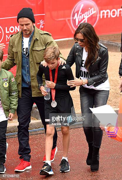 David Beckham and Victoria Beckham congratulate Romeo Beckham after he completed the Junior Marathon during the London Marathon on April 26 2015 in...