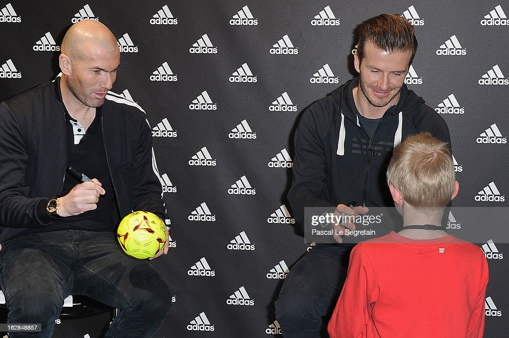 David Beckham (R) and Zinedine Zidane (L) meet with a young fan as they attend an autograph session at adidas Performance Store Champs-Elysees on February 28, 2013 in Paris, France.