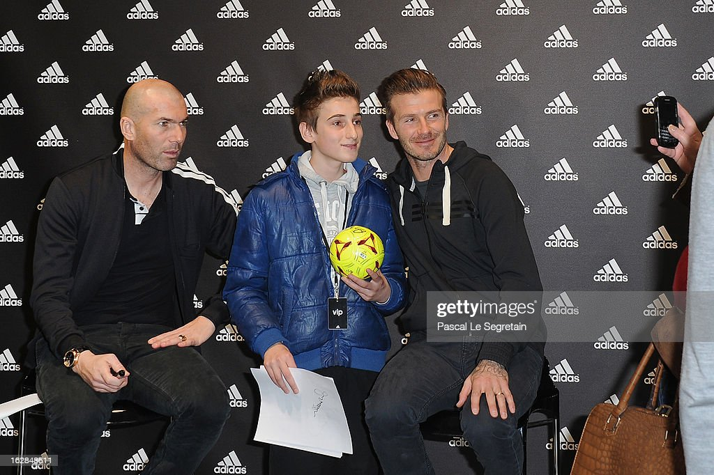 David Beckham (R) and Zinedine Zidane (L) pose with a young fan as they attend an autograph session at adidas Performance Store Champs-Elysees on February 28, 2013 in Paris, France.