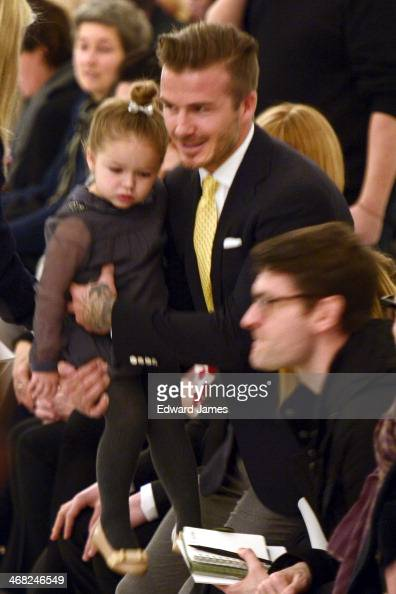 David Beckham carries baby Harper Seven into the front row at the Victoria Beckhamshow during MercedesBenz Fashion Week Fall 2014 at Cafe Rouge on...