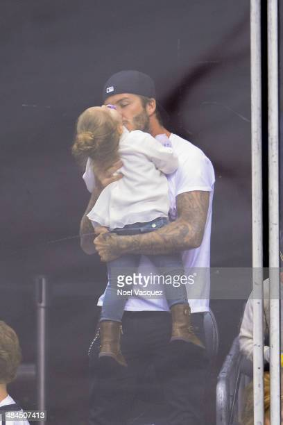 David Beckham kisses Harper Beckham at a hockey game between the Anahiem Ducks and the Los Angeles Kings at Staples Center on April 12 2014 in Los...