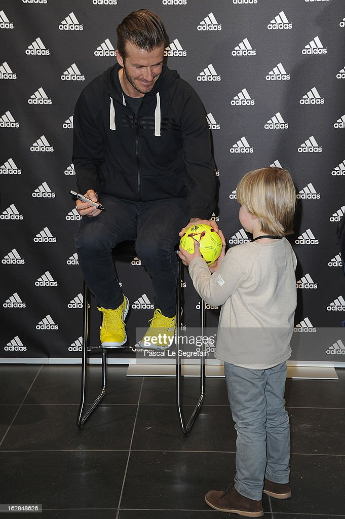 David Beckham (L) meets with a young fan as he attends an autograph session at adidas Performance Store Champs-Elysees on February 28, 2013 in Paris, France.