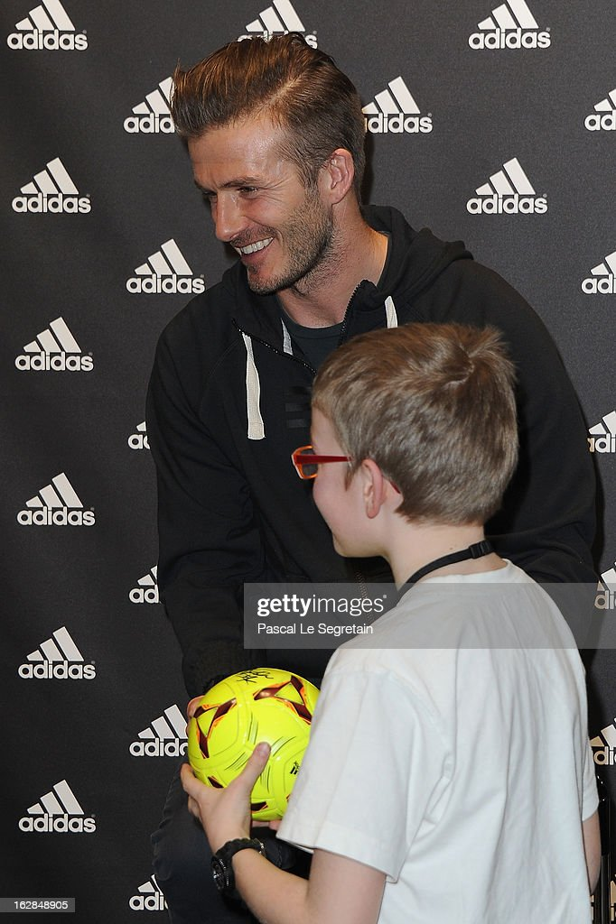 David Beckham meets with a young fan as he attends an autograph session at adidas Performance Store Champs-Elysees on February 28, 2013 in Paris, France.
