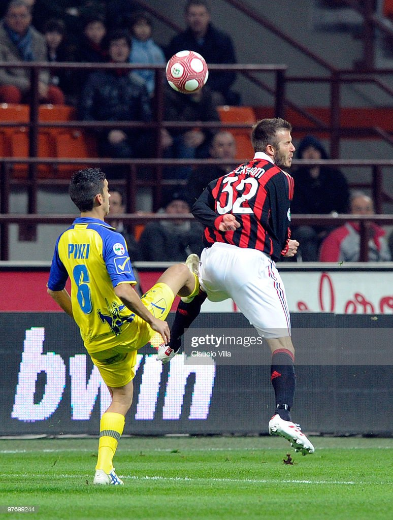David Beckham of AC Milan competes for the ball with Giampiero Pinzi of AC Chievo during the Serie A match between AC Milan and AC Chievo Verona at Stadio Giuseppe Meazza on March 14, 2010 in Milan, Italy.