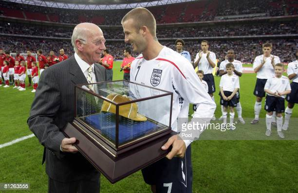 David Beckham of England receives his 100th cap from Sir Bobby Charlton before the International Friendly match between England and USA at Wembley...