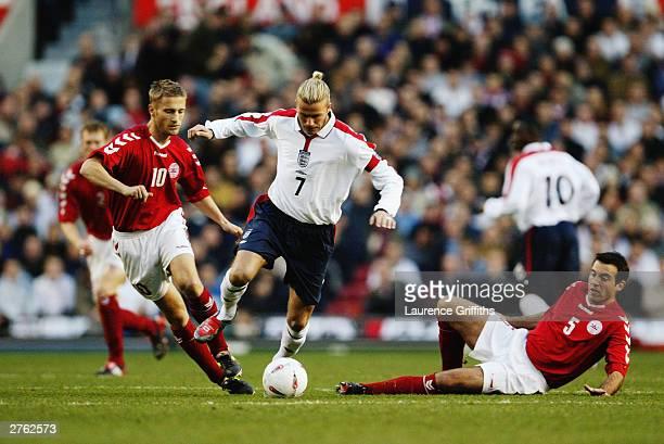 David Beckham of England takes the ball past Niclas Jensen and Martin Jorgensen of Denmark during the International Friendly match between England...