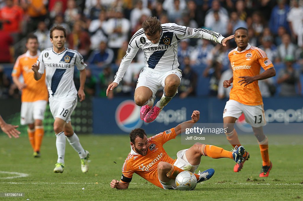 David Beckham #23 of Los Angeles Galaxy leaps over Brad Davis #11 of Houston Dynamo in the second half in the 2012 MLS Cup at The Home Depot Center on December 1, 2012 in Carson, California.