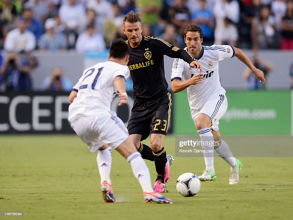 David Beckham of Los Angeles Galaxy maneuvers the ball in between Gonzalo Higuaín and José Maria Callejón of Real Madrid during the World Football...