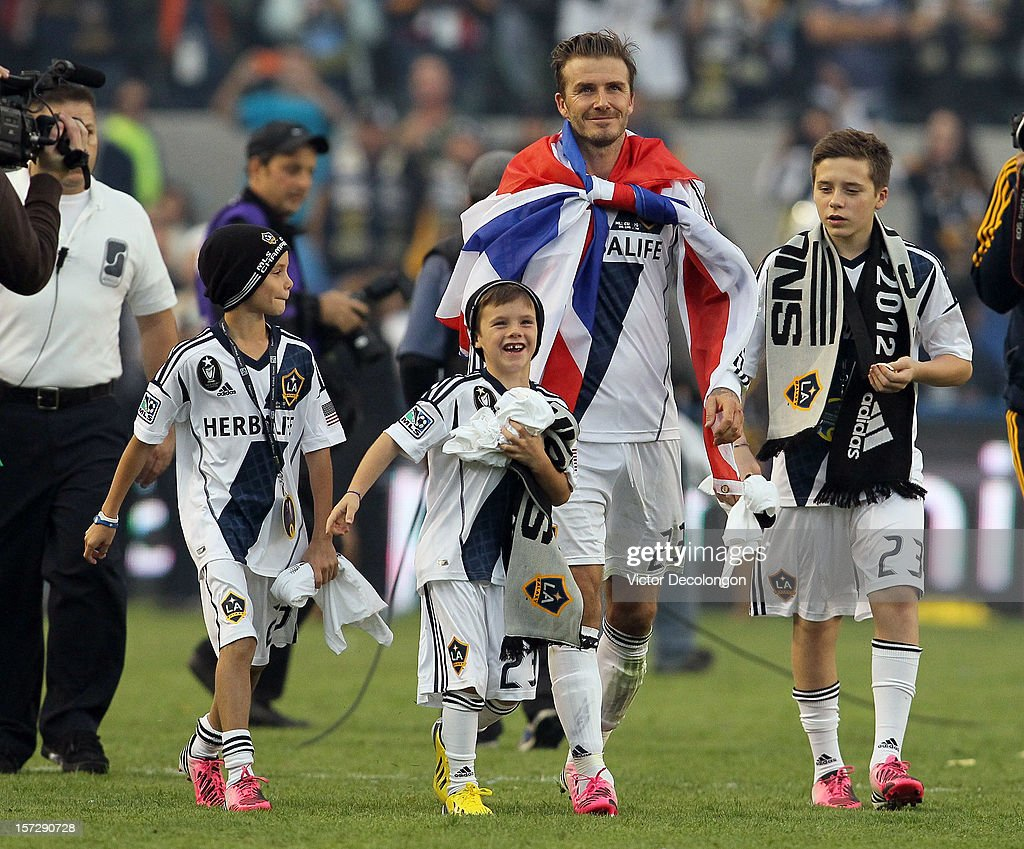 <a gi-track='captionPersonalityLinkClicked' href=/galleries/search?phrase=David+Beckham&family=editorial&specificpeople=158480 ng-click='$event.stopPropagation()'>David Beckham</a> #23 of Los Angeles Galaxy walks off the field with his sons <a gi-track='captionPersonalityLinkClicked' href=/galleries/search?phrase=Romeo+Beckham&family=editorial&specificpeople=171832 ng-click='$event.stopPropagation()'>Romeo Beckham</a>, Cruz Beckham and <a gi-track='captionPersonalityLinkClicked' href=/galleries/search?phrase=Brooklyn+Beckham&family=editorial&specificpeople=214623 ng-click='$event.stopPropagation()'>Brooklyn Beckham</a> after the Galaxy defeat the Houston Dynamo 3-1 to win the 2012 MLS Cup at The Home Depot Center on December 1, 2012 in Carson, California.