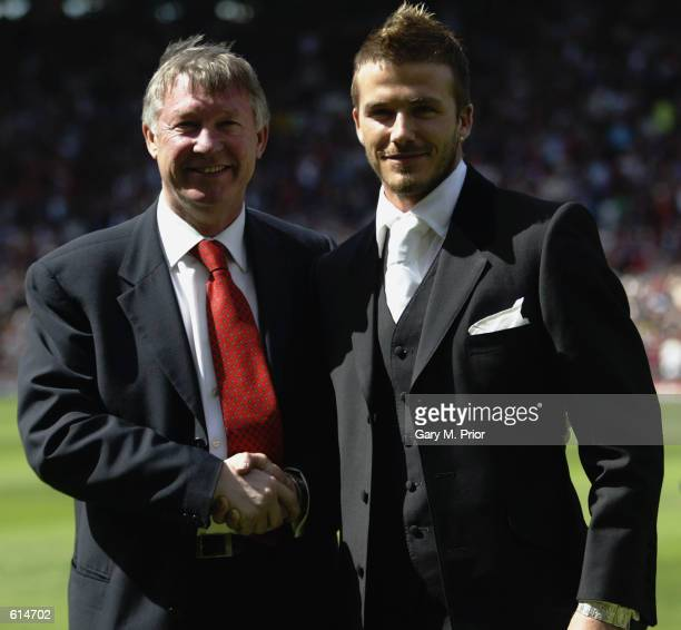 David Beckham of Manchester United and manager Alex Ferguson stand next to each other on the pitch after Beckham signed a new lucrative contract to...