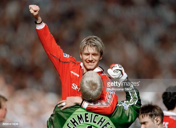David Beckham of Manchester United being lifted by team mate Peter Schmeichel while celebrating winning the FA Cup Final between Manchester United...