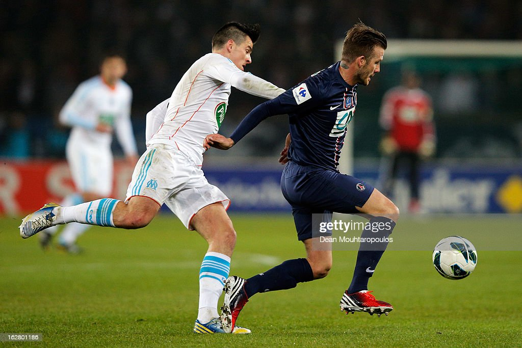 David Beckham of PSG controls the ball and gets past Joey Barton of Marseille during the French Cup match between Paris Saint-Germain FC and Marseille Olympic OM at Parc des Princes on February 27, 2013 in Paris, France.
