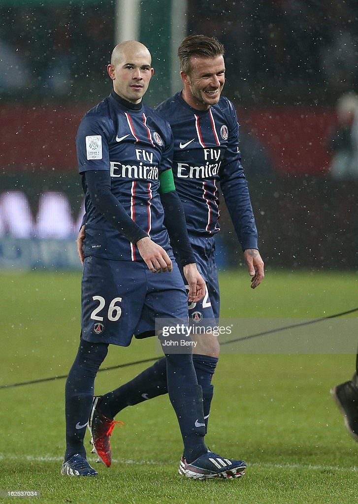 David Beckham of PSG smiles with teammate Christophe Jallet after the French Ligue 1 match between Paris Saint Germain FC and Olympique de Marseille at the Parc des Princes stadium on February 24, 2013 in Paris, France.