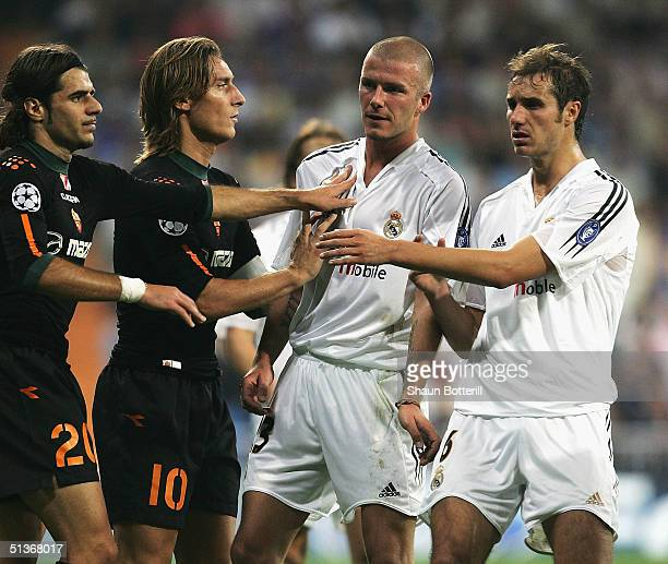 David Beckham of Real Madrid is held back by teammate Ivan Helguera and Simone Perrotta and Francesco Totti of Roma during the UEFA Champions League...