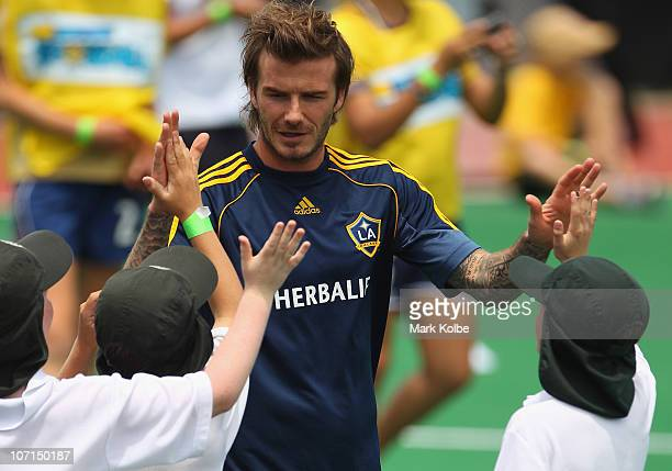 David Beckham of the Galaxy high fives with school children during an LA Galaxy and Newcastle Jets Children's Football Clinic at Newcastle...