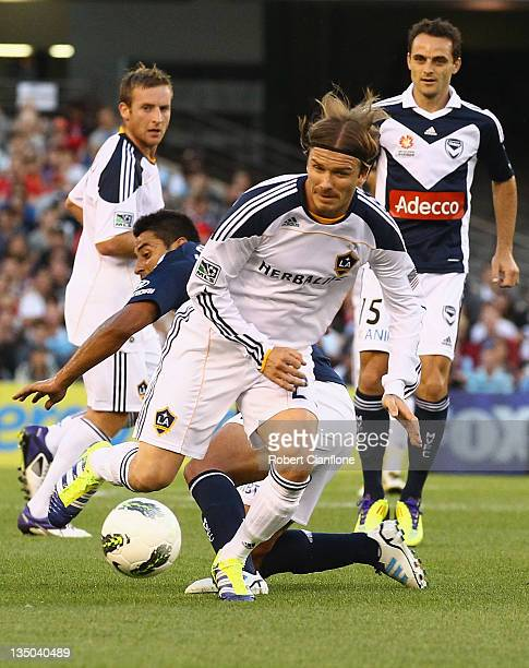 David Beckham of the LA Galaxy is tackled by Carlos Hernandez of the Victory during the friendly match between the Melbourne Victory and LA Galaxy at...