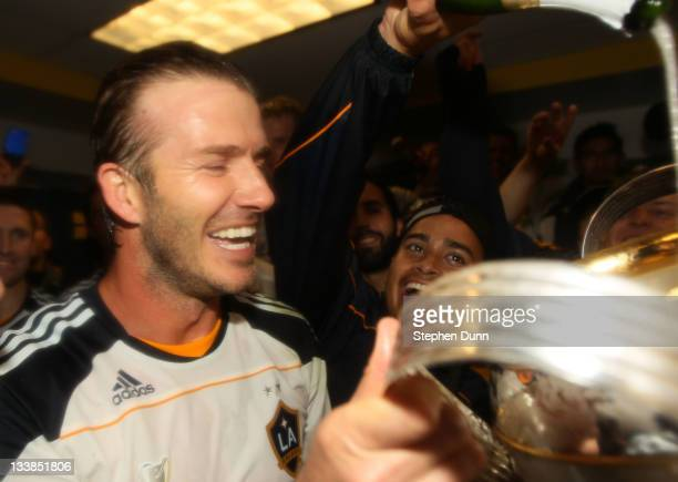 David Beckham of the Los Angeles Galaxy celebrates with the Philip F Anschutz Trophy in the locker room after defeating the Houston Dynamo 10 in the...