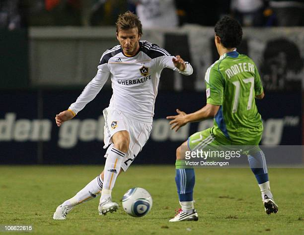 David Beckham of the Los Angeles Galaxy dribbles the ball against Fredy Montero of Seattle Sounders FC during the MLS Western Conference Semifinal...