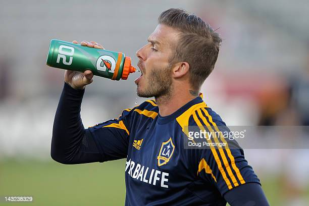 David Beckham of the Los Angeles Galaxy takes a drink as he warms up prior to facing the Colorado Rapids at Dick's Sporting Goods Park on April 21...