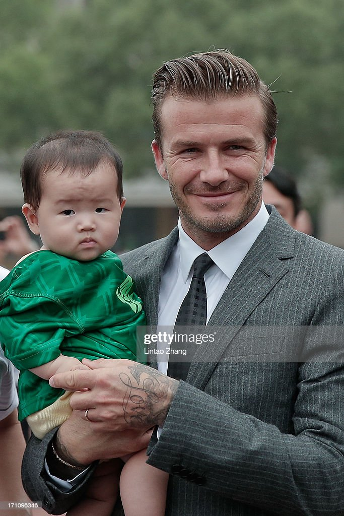 David Beckham poses with a young fan during his visit to Hangzhou Greentown club on June 22, 2013 in Hangzhou, China.