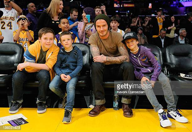 David Beckham poses with his children Brooklyn Beckham Cruz Beckham and Romeo Beckham during the NBA basketball match between Los Angeles Lakers and...