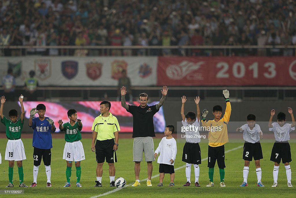 David Beckham poses with young fans during his visit Hangzhou Huanglong Stadium on June 22, 2013 in Hangzhou, China.