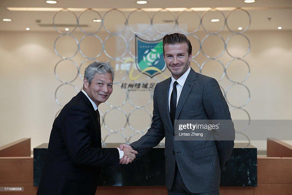 David Beckham (R) shake hands with Shen Qiang, manager of Hangzhou Greentown club on June 22, 2013 in Hangzhou, China.