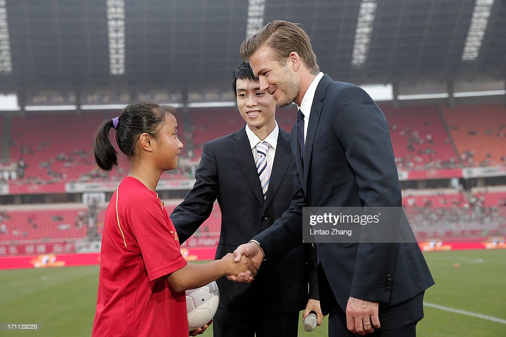 David Beckham (R) shake hands with young fans during his visit Hangzhou Huanglong Stadium on June 22, 2013 in Hangzhou, China.