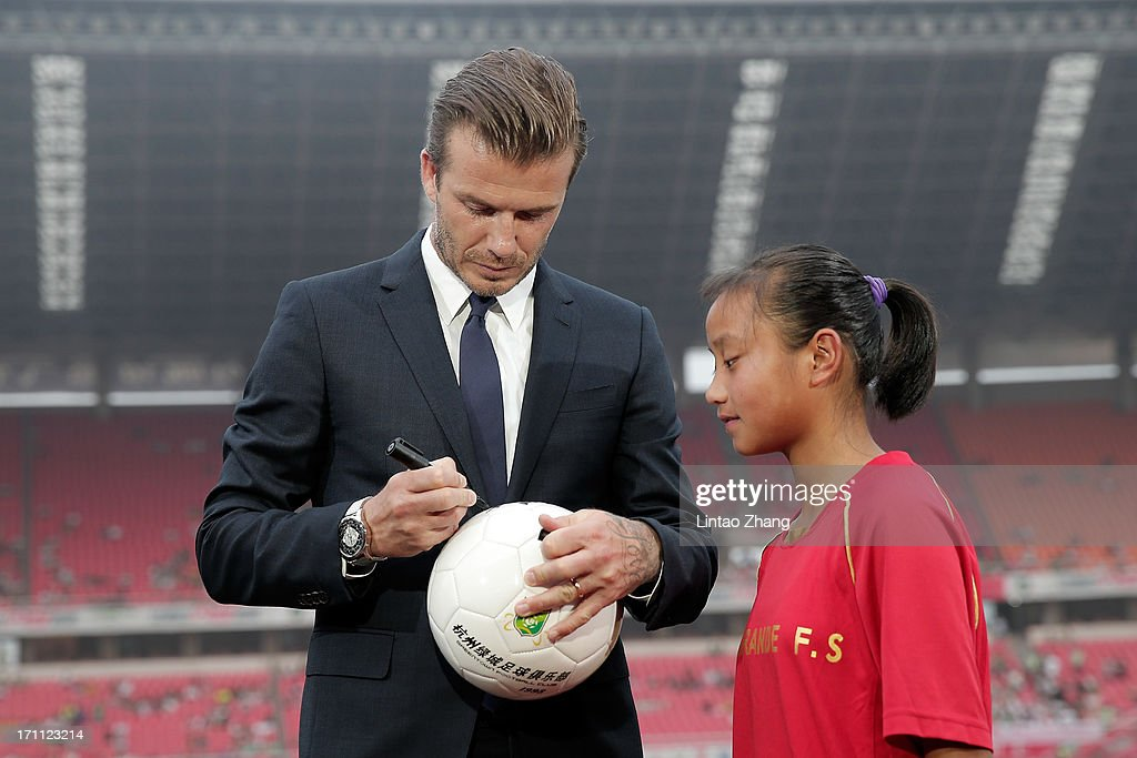 David Beckham signs for young fans during his visit Hangzhou Huanglong Stadium on June 22, 2013 in Hangzhou, China.