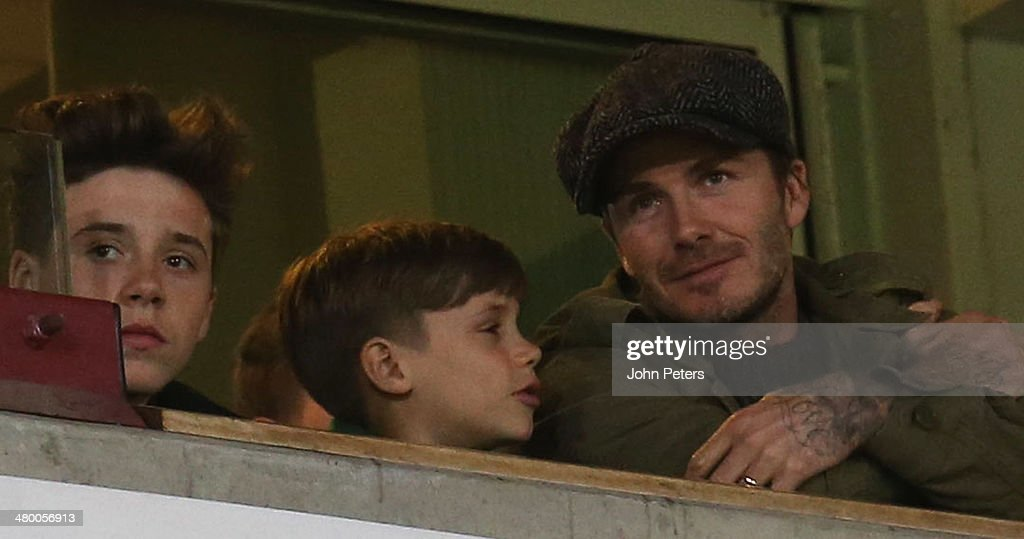 David Beckham watches from an executive box with his sons Brooklyn (L) and Cruz during the Barclays Premier League match between West Ham United and Manchester United at Boleyn Ground on March 22, 2014 in London, England.