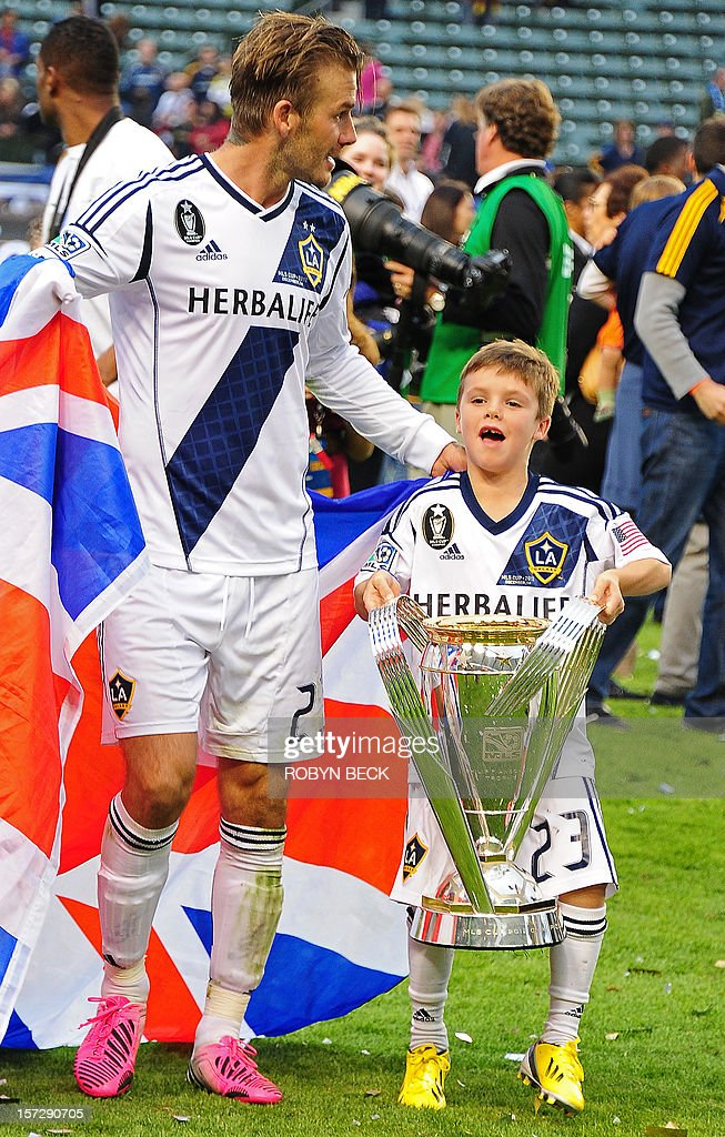 David Beckham's son Cruz lifts the MLS Trophy after the Los Angeles Galaxy were awarded the trophy for their 3-1 victory over the Houston Dynamo in the final of the Major League Soccer (MLS) Cup against Houston Dynamo, December 1, 2012 in Carson, California. It was Beckham's last game with the Galaxy. AFP PHOTO / Robyn Beck