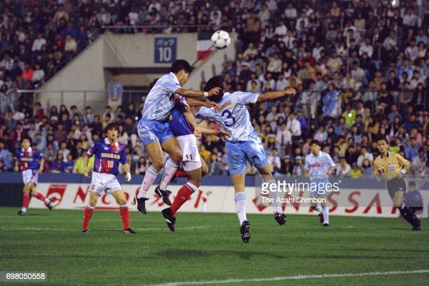 David Bisconti of Yokohama Marinos competes for the ball against Takeshi Yonezawa and Masahiro Endo of Jubilo Iwata during the JLeague match between...