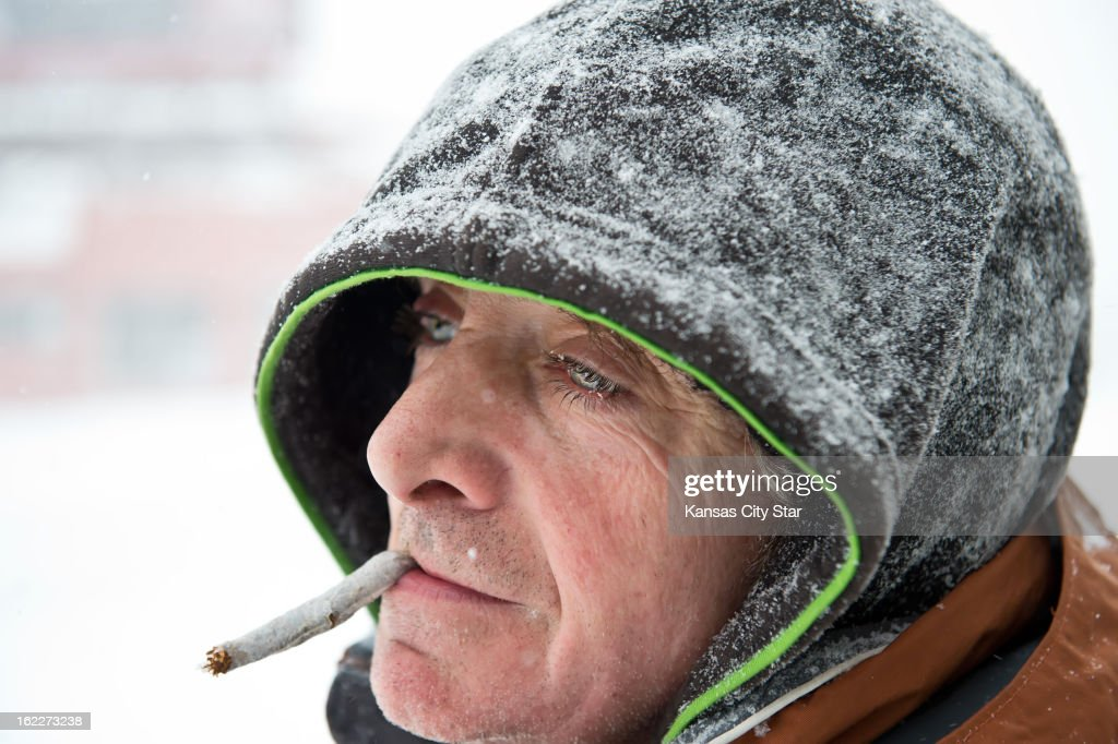 David Black smokes his own tobacco cigarette during a break in shoveling snow at 40th & Broadway Boulevard in Kansas City, Missouri, during snowstorm, Thursday, February 21, 2013. 'It's just tobacco, it's not a 'doobie,' be sure to put that down,' Black said.