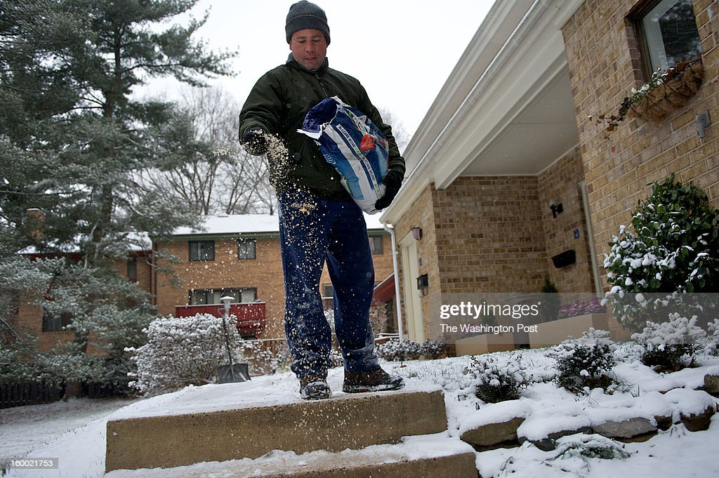 David Bonner pours salt in front of his home in Reston, VA. The DC Metro Area got hit with it's first snow fall of the year.
