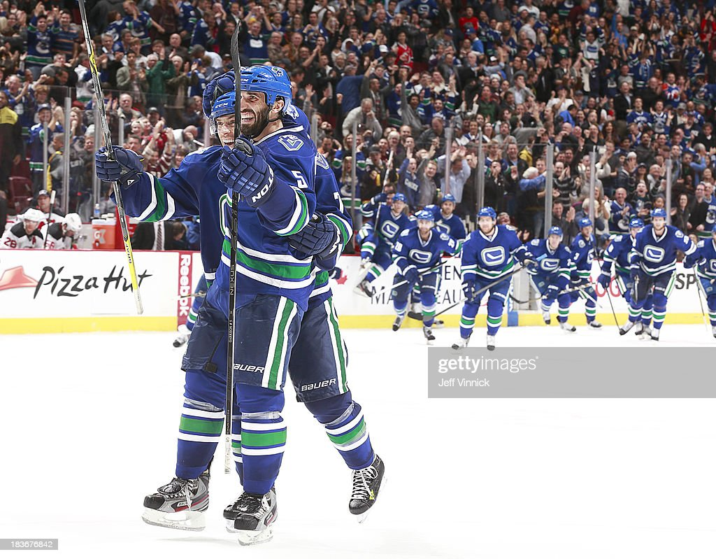 <a gi-track='captionPersonalityLinkClicked' href=/galleries/search?phrase=David+Booth+-+Ice+Hockey+Player&family=editorial&specificpeople=1109572 ng-click='$event.stopPropagation()'>David Booth</a> #7 congratulates <a gi-track='captionPersonalityLinkClicked' href=/galleries/search?phrase=Jason+Garrison&family=editorial&specificpeople=2143635 ng-click='$event.stopPropagation()'>Jason Garrison</a> #5 of the Vancouver Canucks who scored in overtime against the New Jersey Devils during their NHL game at Rogers Arena on October 8, 2013 in Vancouver, British Columbia, Canada. Vancouver won 3-2.