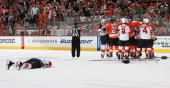David Booth of the Florida Panthers lies on the ice after a hit by Mike Richards of the Philadelphia Flyers as both teams tangle in a scrum on...