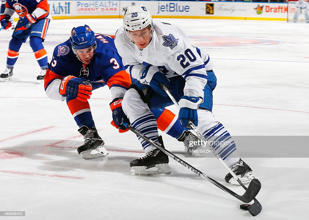 David Booth of the Toronto Maple Leafs is pursued by Travis Hamonic of the New York Islanders at Nassau Veterans Memorial Coliseum on February 12...