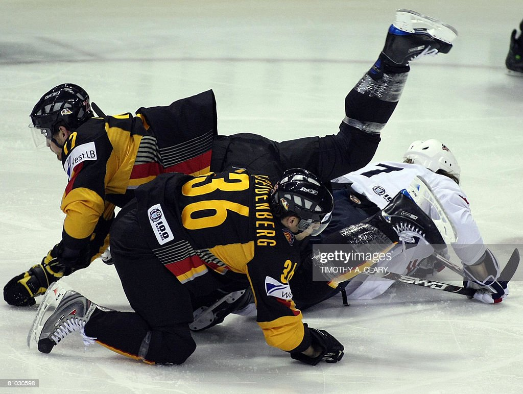 David Booth of the US gets checked by Germany's Michael Bakos and Yannic Seidenberg during the qualification round of the 2008 IIHF World Hockey...