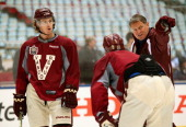 David Booth of the Vancouver Canucks and goaltender coach Roland Melanson attend practice for the 2014 Tim Hortons NHL Heritage Classic game against...
