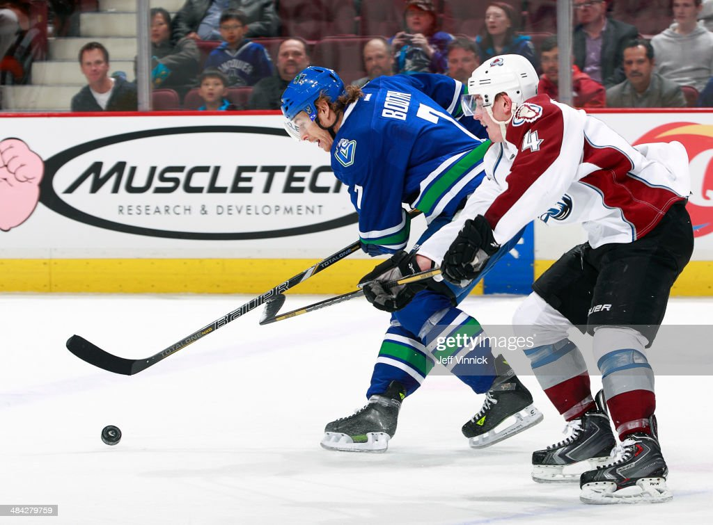 David Booth of the Vancouver Canucks and Tyson Barrie of the Colorado Avalanche battle for a loose puck during their NHL game at Rogers Arena April...